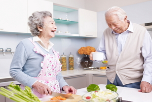 An elderly couple cooking in the kitchen together.