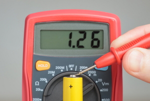 A multimeter testing the end of a battery.