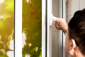 man opening a metal casement window