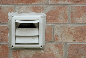 An exterior dryer vent outside of a brick house.