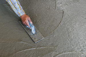 man spreading self-leveling compound on a floor