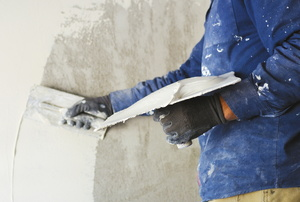 A DIYer plastering a concrete wall.
