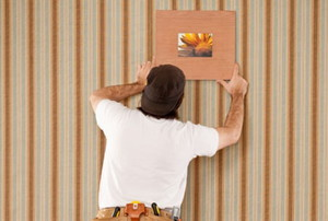 man hanging artwork on a wallpapered wall