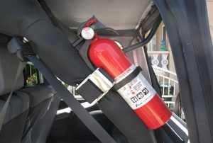 A fire extinguisher secured in the trunk of a vehicle.