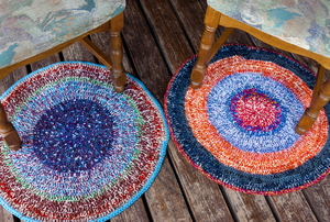 two colorful rugs sitting under chair on wood flooring
