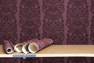Rolls of damask wallpaper sitting on a table, ready for wallpapering.