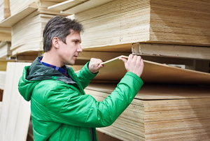 A man in a green jack choosing plywood.