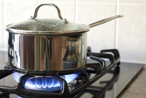 A gas stove with a pot on it.