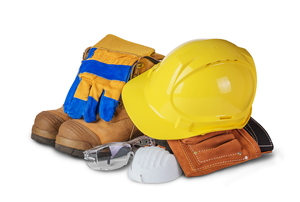 A pile of safety gear including a hard hat and gloves against a white background.