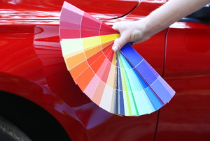 Paint swatches in front of a red car.