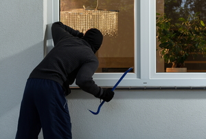 Burglar breaking into home window
