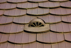 A stylized roof vent surrounded by matching brown tiles.