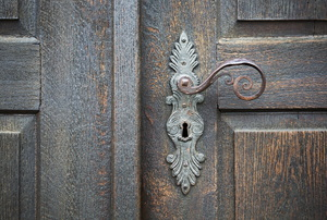 A wood door with a decorative handle.