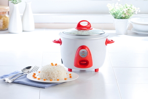 A small white and red rice cooker sitting on a counter beside a dish of prepared white rice.