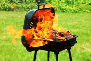 A portable barbeque outdoors with the large flames of a flash fire coming out.