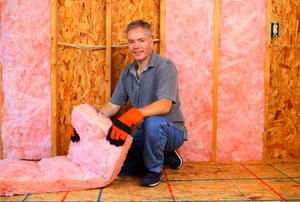 A man preparing to install pink fiberglass insulation in a wall.