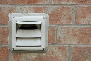 white dryer vent mounted in a brick wall