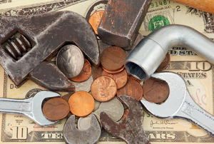 A pile of coins and cash with hand tools.