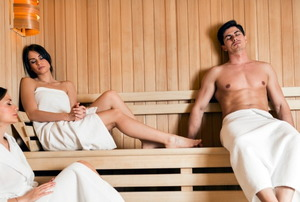 three people in towels lounging in a sauna