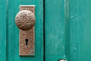 closeup of a teal door with doorknob