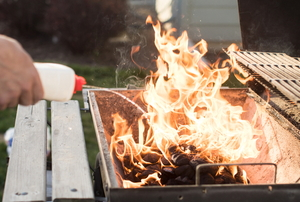 hand applying lighter fluid to bbq grill