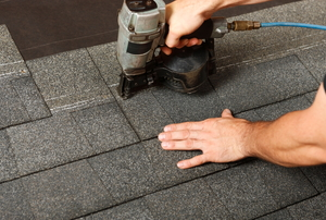 A man applies asphalt shingles.