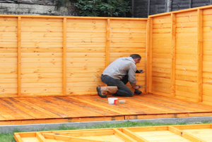A man builds a shed.