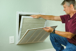 A man checking out an HVAC vent in a wall.