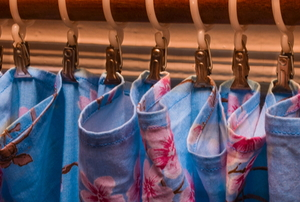 fabric shower curtain hanging on wood rings