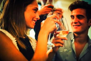 A young man and woman clinking glasses of white wine at a party.