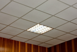 A square, fluorescent lighting fixture in a tiled ceiling.