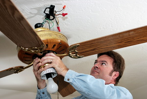 A man wiring a ceiling fan.