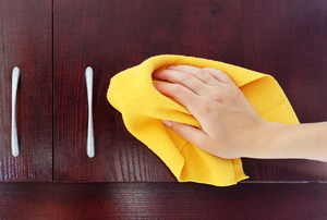a hand cleaning a kitchen cupboard.