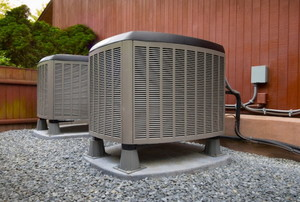 two air conditioning units on the side of a building