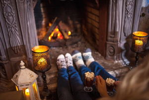A couple people sitting in front of a fireplace with candles and cups of hot chocolate.