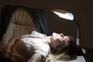 A woman sits under a SAD lamp.
