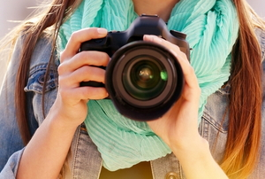 woman with long hair, scarf, and large camera