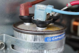 A close image of an air conditioner capacitor.