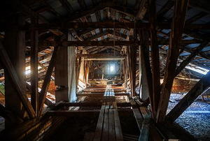 Looking down the length of a long, dark attic with unevenly-spaced floor boards.