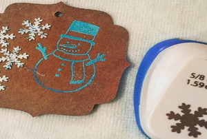 A gift tag with a snowman and snowflakes on it next to a craft punch.