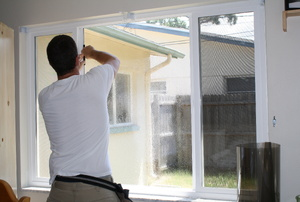 A man works on window film.