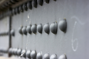 Several rows of solid rivets used to fasten a metal girder.