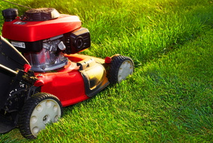 A red lawn mower cutting grass.