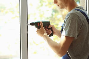 A man using a drill on a window.