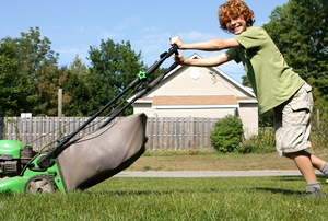 A red-headed boy mowing the lawn with a bagged push mower.