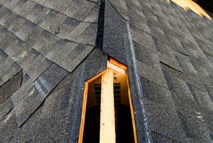 The hole for a ridge vent on a partially-shingled roof.