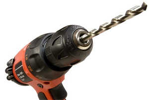 A close-up of the drill bit on a black and orange drill.