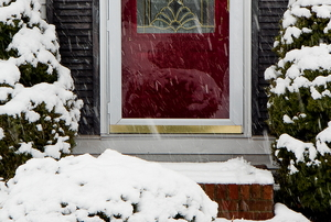 Snow falling on the brick step of a home with a white storm door.