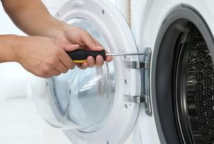 hands repairing washing machine