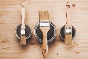 Paint brushes and cans of paint on wood